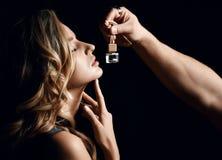 Retrato ascendente cercano del perfume auto del olor hermoso atractivo de la mujer en oscuridad imagen de archivo libre de regalías