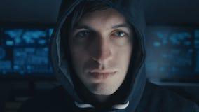 Retrato ascendente cercano del programador del pirata informático en sudadera con capucha negra en el fondo del centro cibernétic almacen de video