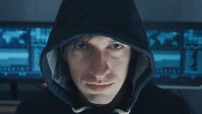 Retrato ascendente cercano del programador profesional del pirata informático de las TIC en sudadera con capucha negra en el cent almacen de video