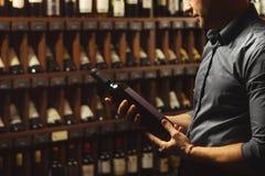 Retrato ascendente cercano del sommelier que sostiene la botella de vino en fondo de la bodega fotografía de archivo