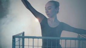 Retrato ascendente próximo da dança profissional graciosa da bailarina no vestido preto no estúdio dentro da gaiola azul dentro vídeos de arquivo