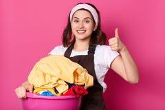 Retrato ascendente próximo da dona de casa delgada bonita que guarda a bacia cor-de-rosa com roupa limpa, tendo a expressão facia fotografia de stock royalty free