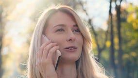Retrato ascendente próximo da mulher caucasiano na moda bonita que fala no smartphone, apreciando o passeio no parque do outono M video estoque