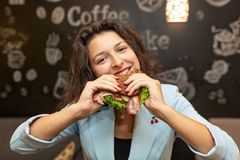 Retrato ascendente próximo da mulher caucasiano nova com fome, sanduíche da mordida imagens de stock royalty free