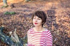 Retrato ascendente próximo da mulher de sorriso nova com os olhos fechados que sentam-se e que relaxam na árvore caída no outono  imagens de stock