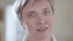 Retrato ascendente próximo da mulher superior que olha in camera com sorriso agradável dentro O fundo é borrado video estoque