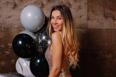 Retrato ascendente próximo da senhora bonita de sorriso com o cabelo longo louro que veste sparcly o vestido que olha a câmera e  foto de stock
