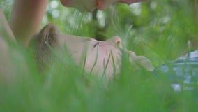 Retrato ascendente próximo da testa de beijo da menina do menino que encontra-se na grama Um par crianças felizes engra?ado filme
