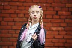 Retrato ascendente próximo de pouca menina à moda bonita da criança perto da parede de tijolo vermelho como o fundo foto de stock royalty free