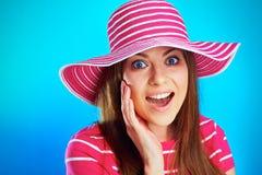 Retrato ascendente próximo de sorriso surpreendido jovens da mulher contra o azul Fotografia de Stock Royalty Free