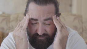 Retrato ascendente próximo de um homem farpado que esteja sofrendo de uma dor de cabeça, friccionando sua cabeça com suas mãos vídeos de arquivo