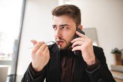 Retrato ascendente próximo de um homem de negócio que senta-se em um café claro, falando no telefone, comendo uma forquilha do al fotografia de stock