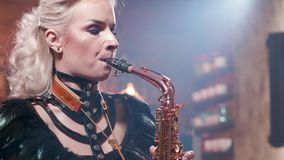 Retrato ascendente próximo de um saxofonista fêmea em um concerto vivo do jazz filme