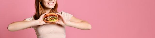 Retrato ascendente próximo de uma jovem mulher com fome que come o hamburguer sobre o fundo cor-de-rosa fotos de stock