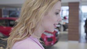Retrato ascendente próximo de uma menina bem sucedida feliz com o cabelo louro que escolhe um carro novo na feira automóvel da el vídeos de arquivo