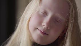 Retrato ascendente próximo de uma menina do albino com os olhos cinzentos que olham o sorriso da câmera Apar?ncia incomum Inf?nci vídeos de arquivo
