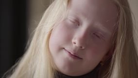 Retrato ascendente próximo de uma menina do albino com os olhos cinzentos que olham o sorriso da câmera Apar?ncia incomum Inf?nci filme
