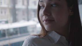 Retrato ascendente próximo de uma mulher bonita que pensa e que olha no café bebendo da janela Mulher bonita que aprecia a quente filme