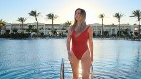 Retrato ascendente próximo disparado da jovem mulher atrativa na piscina vermelha molhada do roupa de banho como um raio no dia e filme
