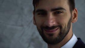 Retrato ascendente próximo do bussinesman considerável novo em escuro - olhar azul do terno in camera e para sorrir movimento len video estoque