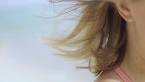 Retrato ascendente próximo do cabelo bonito da jovem mulher que funde no vento na praia tropical 4k video estoque