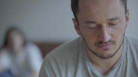 Retrato ascendente próximo do homem de grito no primeiro plano e de sua esposa irritada da gritaria que senta-se no sofá no fundo vídeos de arquivo
