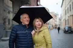 Retrato ascendente pr?ximo do homem idoso e sua de esposa louro-de cabelo nova que abra?am-se e que est?o sob seu guarda-chuva fotos de stock royalty free