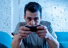 Retrato ascendente próximo do homem novo que joga o jogo de vídeo na noite dedicado a ele imagens de stock