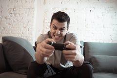 Retrato ascendente próximo do homem novo que joga o jogo de vídeo na noite dedicado a ele fotos de stock