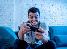 Retrato ascendente próximo do homem novo que joga o jogo de vídeo na noite dedicado a ele que tem o divertimento foto de stock