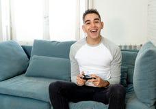 Retrato ascendente próximo do homem novo que joga o jogo de vídeo que tem o divertimento, no apego do jogo de vídeo ou no lazer fotos de stock royalty free