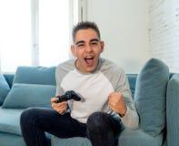 Retrato ascendente próximo do homem novo que joga o jogo de vídeo que tem o divertimento, no apego do jogo de vídeo ou no lazer imagem de stock