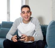 Retrato ascendente próximo do homem novo que joga o jogo de vídeo que tem o divertimento, no apego do jogo de vídeo ou no lazer fotos de stock