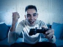 Retrato ascendente próximo do homem novo que tem o divertimento que joga jogos de vídeo No lazer e no conceito do apego do jogo imagem de stock
