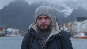 Retrato ascendente próximo do homem sério do cais de Noruega, barco do fundo filme