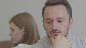 Retrato ascendente próximo do homem triste e da mulher que sentam-se de volta à parte traseira com caras infelizes em casa Proble video estoque