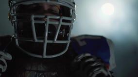 Retrato ascendente próximo do jogador de futebol americano farpado que põe sobre o capacete na cabeça, olhando in camera com calm video estoque