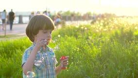 Retrato ascendente próximo do menino bonito pequeno feliz que funde, tendo o divertimento com bolhas de sabão no parque Criança p vídeos de arquivo