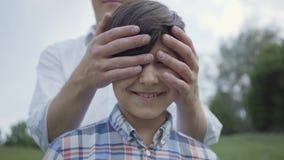 Retrato ascendente próximo do menino bonito que olha na câmera, em seu pai ou no irmão mais idoso cobrindo seus olhos de atrás E vídeos de arquivo