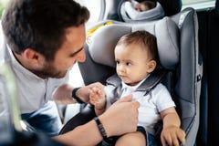 Retrato ascendente próximo do pai novo que fixa o bebê no assento da criança do carro imagem de stock