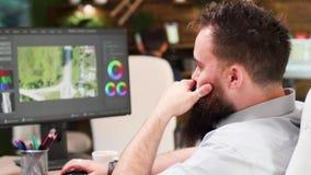 Retrato ascendente próximo do videographer que trabalha no software profissional filme