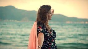 Retrato ascendente próximo uma mulher moreno bonita com os olhos verdes com cabelo de fluxo em um vestido do verão com uma imagem filme