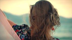 Retrato ascendente próximo uma mulher moreno bonita com os olhos verdes com cabelo de fluxo em um vestido do verão com uma imagem video estoque
