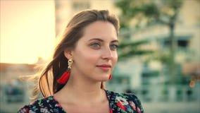 Retrato ascendente próximo uma mulher moreno maravilhosa com os olhos verdes com cabelo de fluxo em um vestido do verão com uma i filme