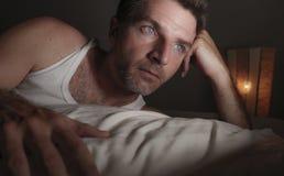 Retrato ascendente pr?ximo da cara do homem triste e pensativo atrativo que encontra-se na cama acordada tarde no sentimento de p foto de stock