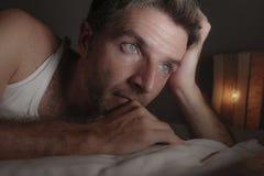 Retrato ascendente pr?ximo da cara do homem triste e pensativo atrativo que encontra-se na cama acordada tarde no sentimento de p fotografia de stock royalty free