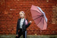 Retrato ascendente pr?ximo de pouca menina ? moda bonita da crian?a com um guarda-chuva na chuva perto da parede de tijolo vermel fotos de stock