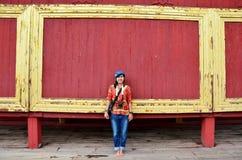 Retrato asiático de la mujer con el fondo rojo de madera en el palacio de Mandalay Imagenes de archivo