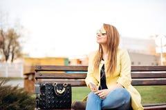 Retrato asombroso de la mujer elegante joven que escucha la música, disfrutando del momento, canción Sentándose en la calle, sost Foto de archivo