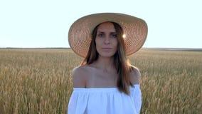 Retrato asombroso de la mujer hermosa que se coloca en campo del trigo de oro maduro metrajes